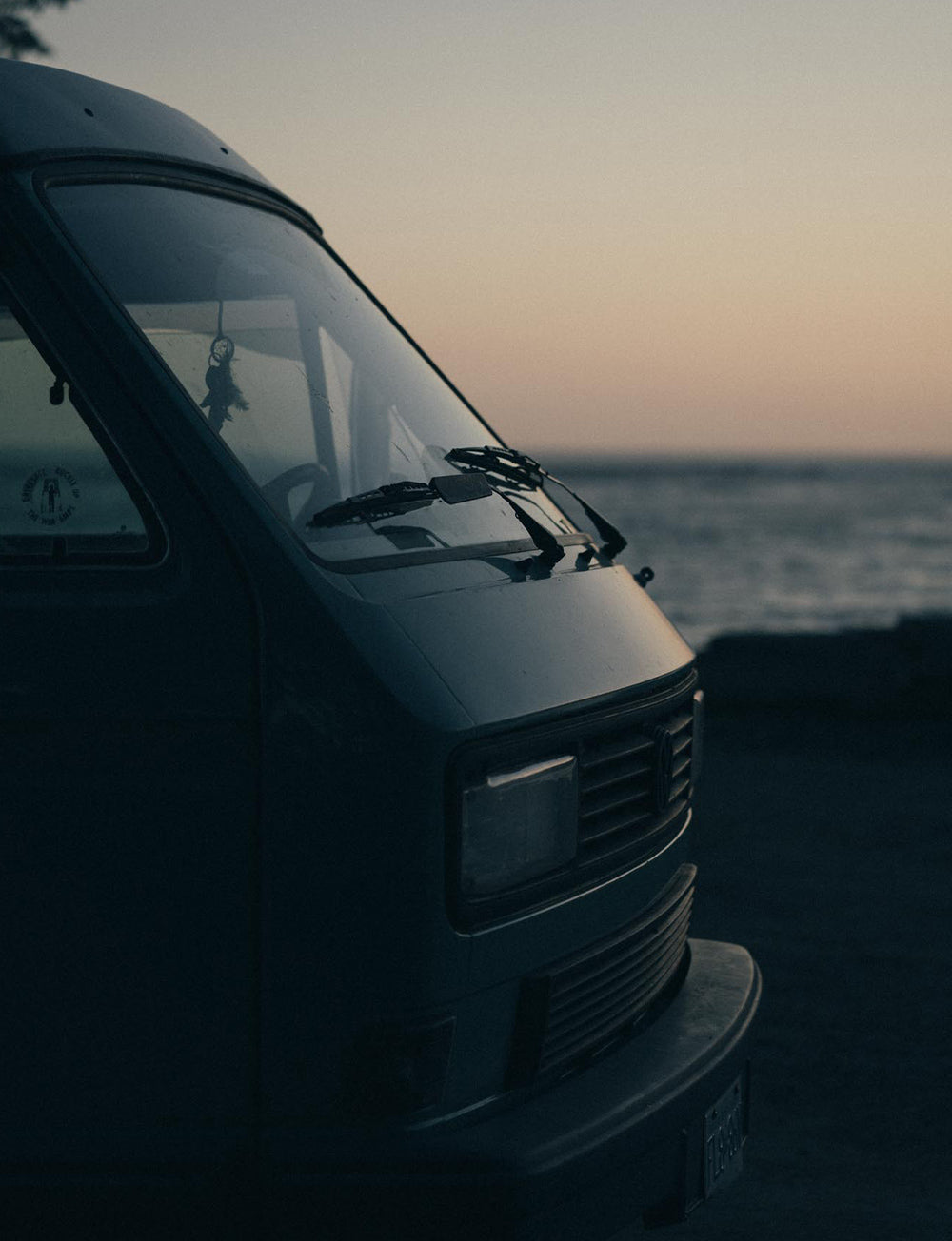 The sunset reflects off the windscreen and bonnet of the classic VW Westy