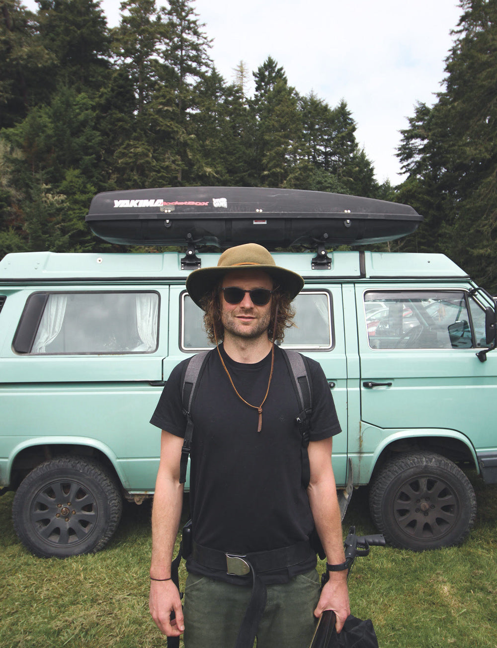 A portrait of Mackenzie Duncan, standing infront of his classic campervan