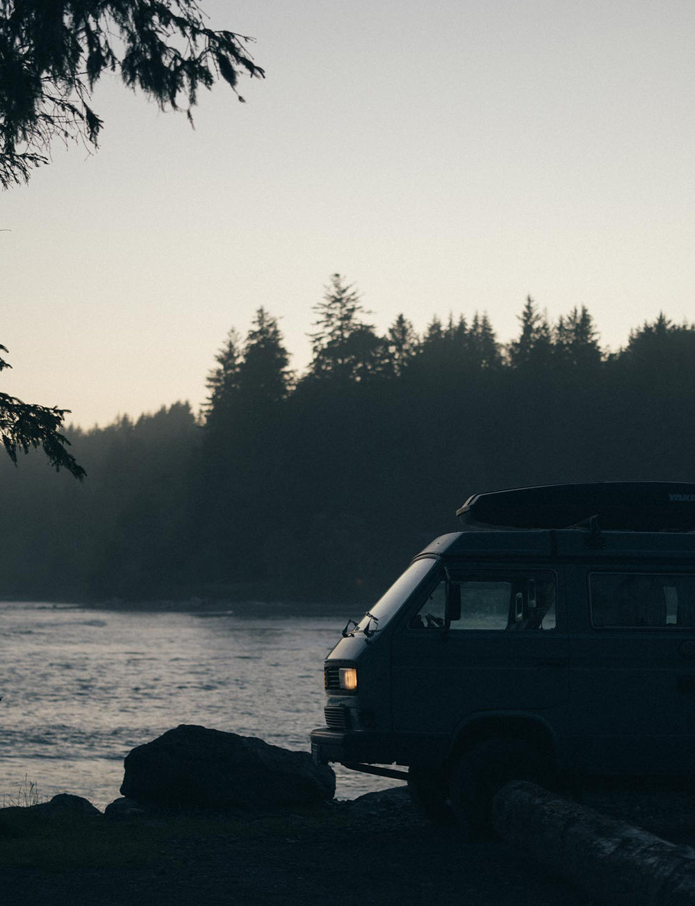 A classic VW Westy sits by the water during blue hour with trees and ocean in the background.
