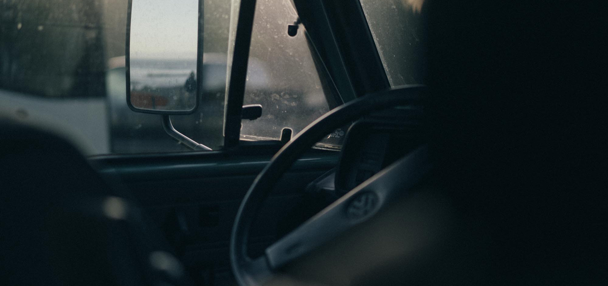 Looking out the window of a classic VW Westy towards waves rolling in.