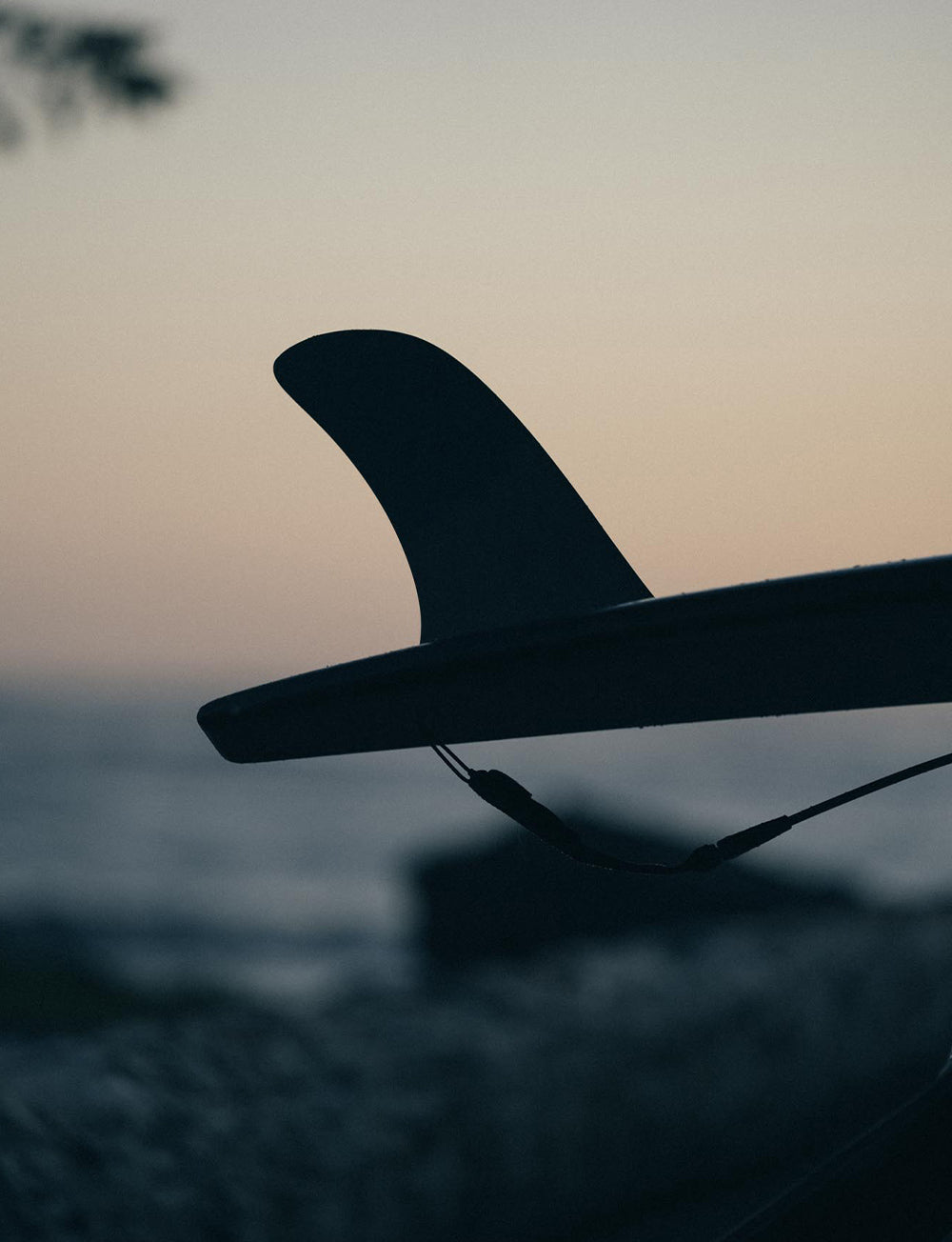 Silhoette of a single-fin longboard surfboard with a dusky sunset background.