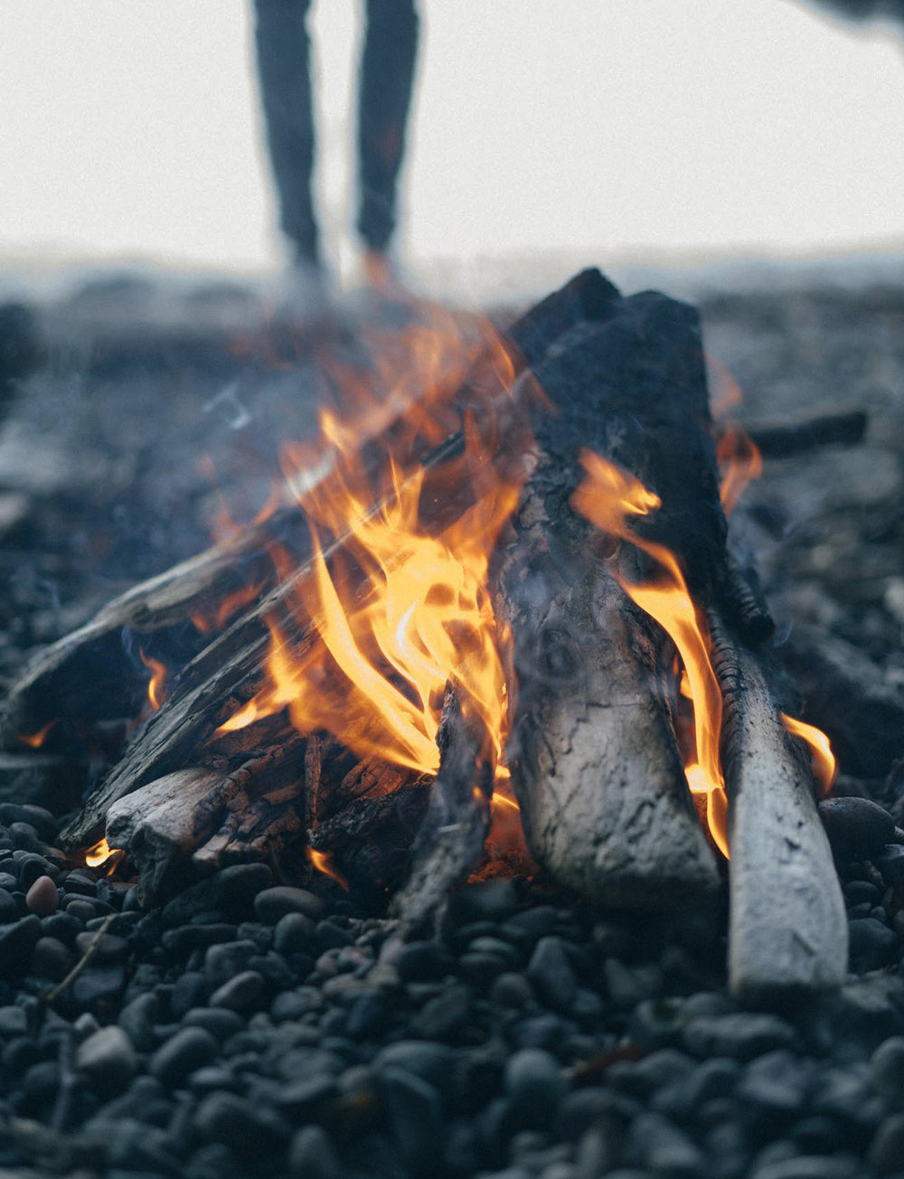 A beach campfire burns on a Canadian shingle beach.
