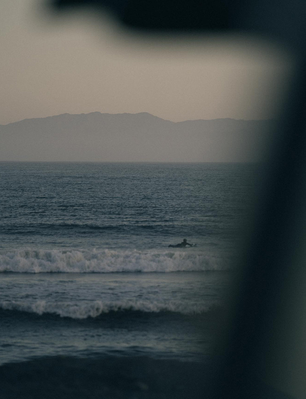 A lone surfer paddles out towards the incoming swell, the sun has set with the silhouette of mountains in the background.