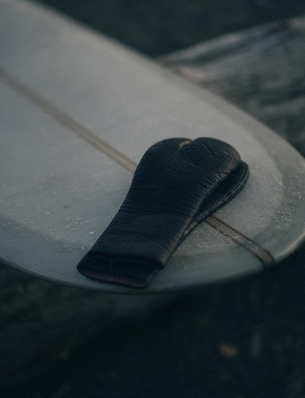 A pair of wet surf gloves sit ontop of a classic longboard surfboard