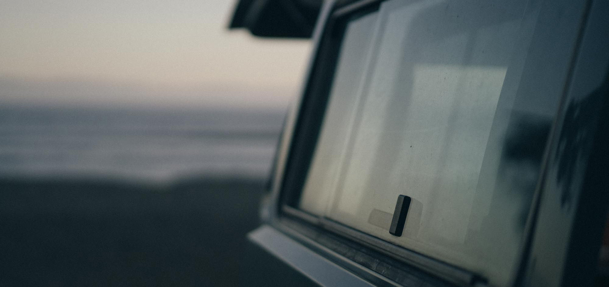 A dusky blue-hour sky reflects off the rear window of a classic VW Westy campervan