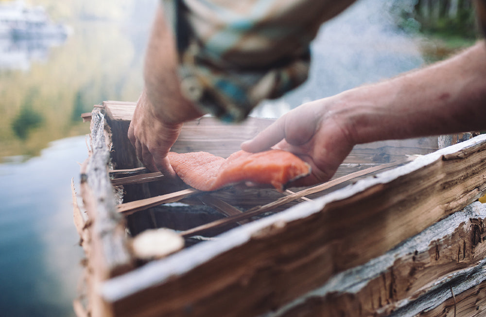 A man smokes freshly caught salmon on a traditional smoker