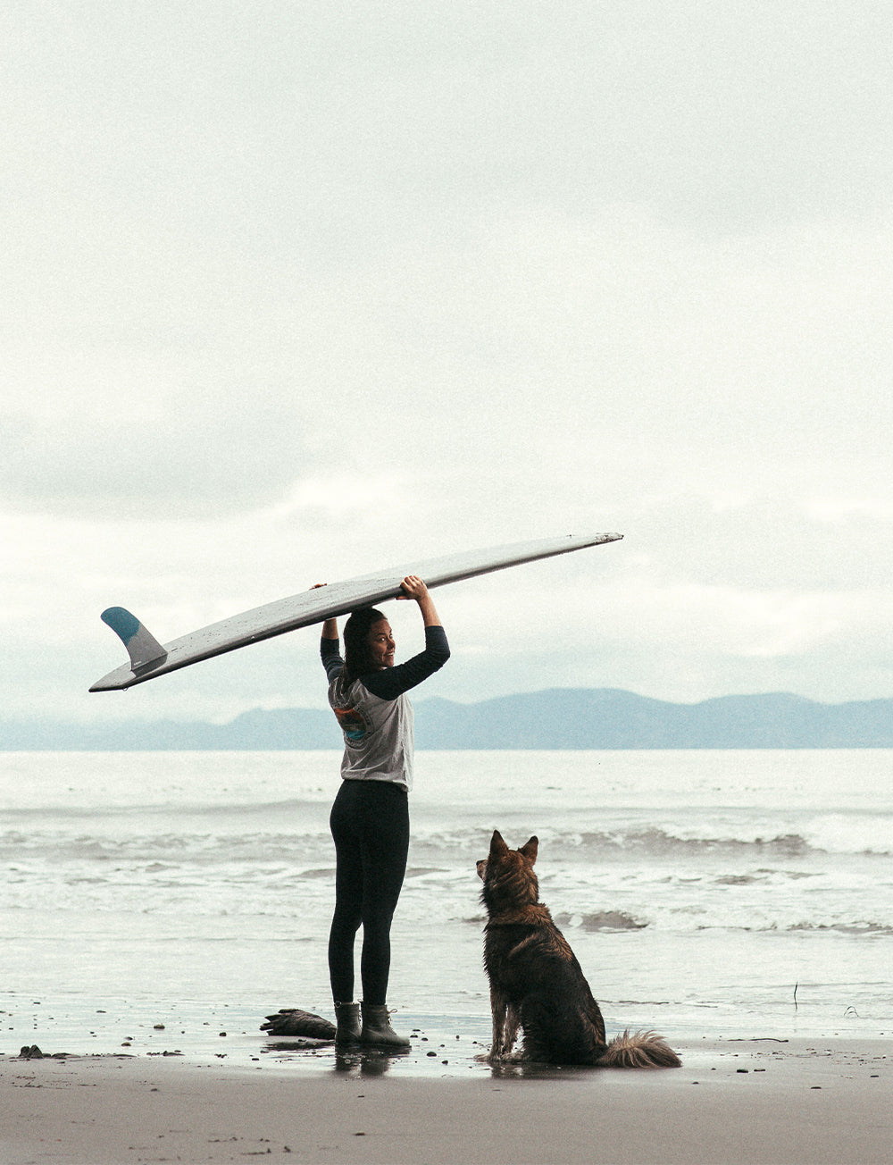 A female surfer with her dog waits for waves