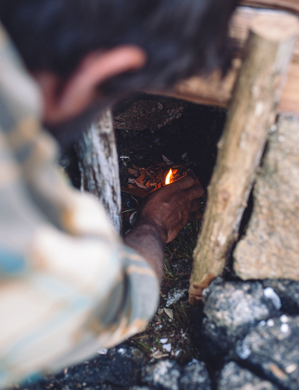 Man tends to a small fire inside a smoke stack