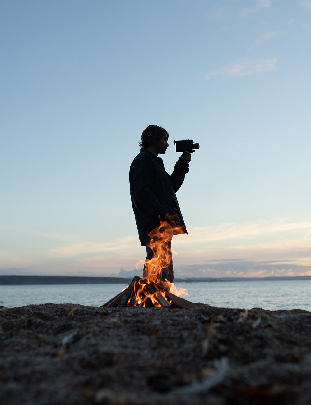 Man looks towards the rising sun with retro super35 camera. Campfire burns infront of him.