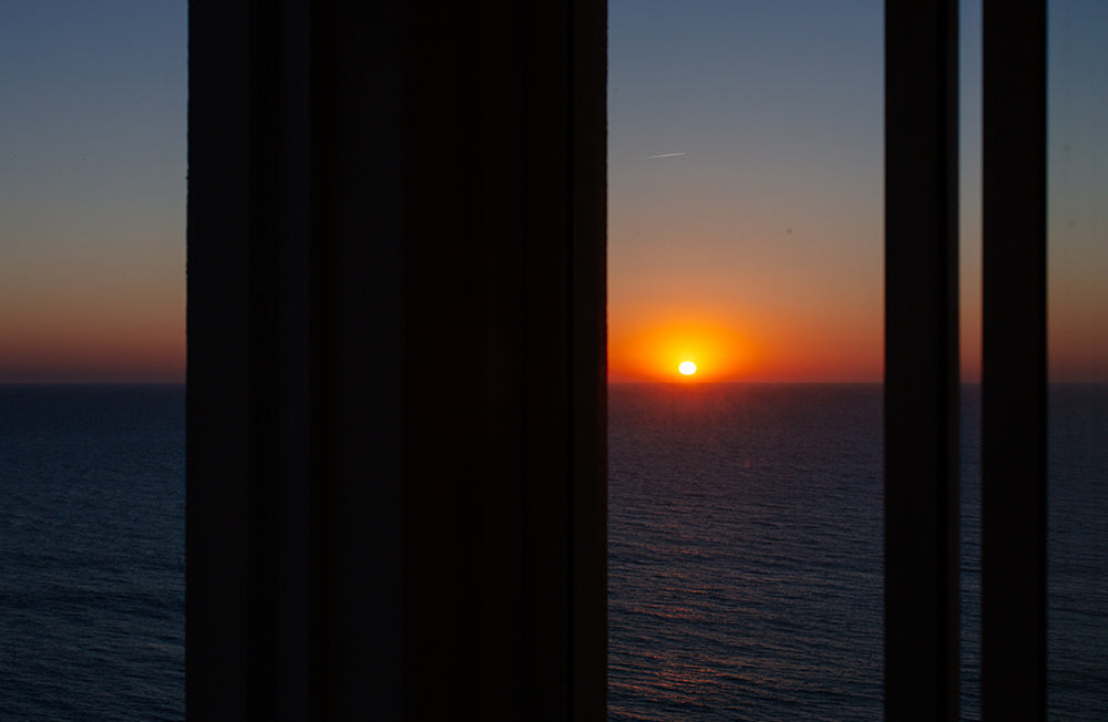 Outside the window, the sun rises over the ocean.