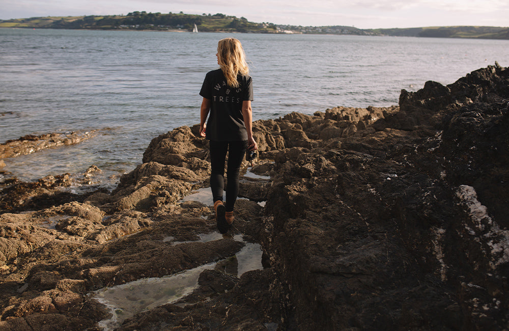 A woman walks along the coastal rocks looking out at the sunrise