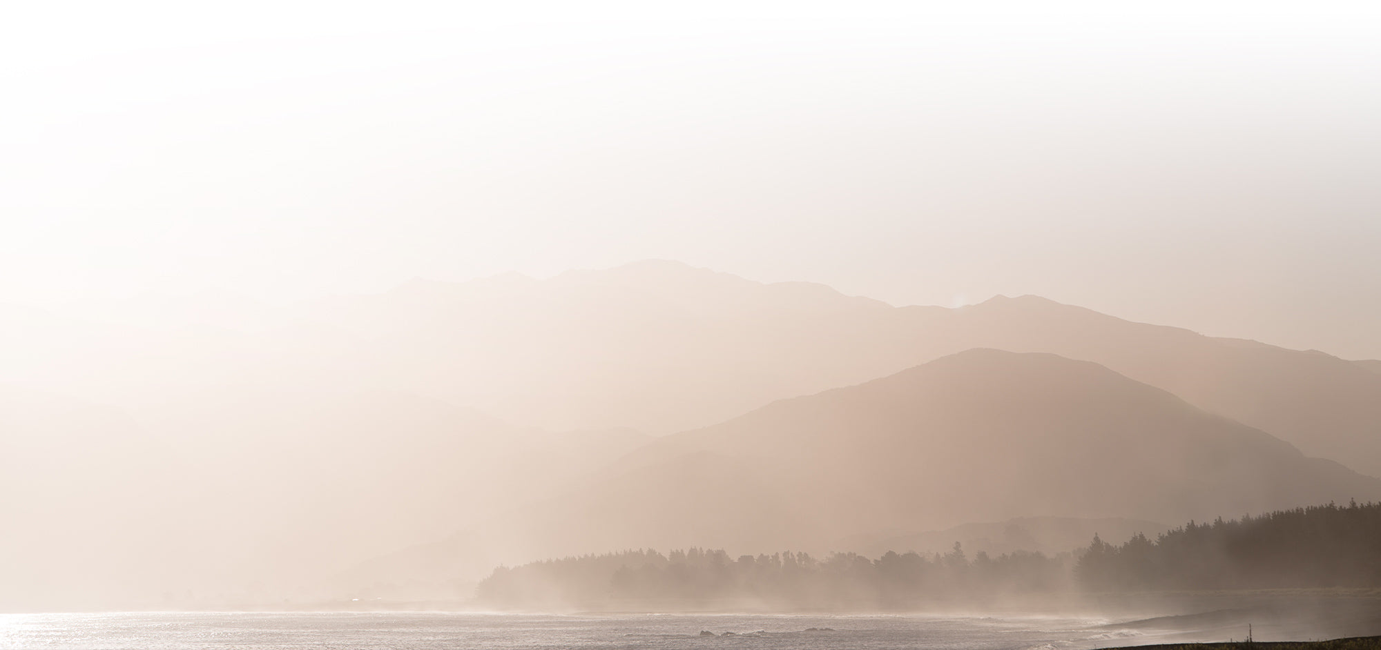 A hazy morning view over mountains, waves and trees.