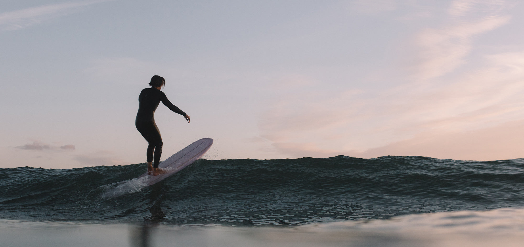 Man stands on his longboard riding over the incoming surf swell.