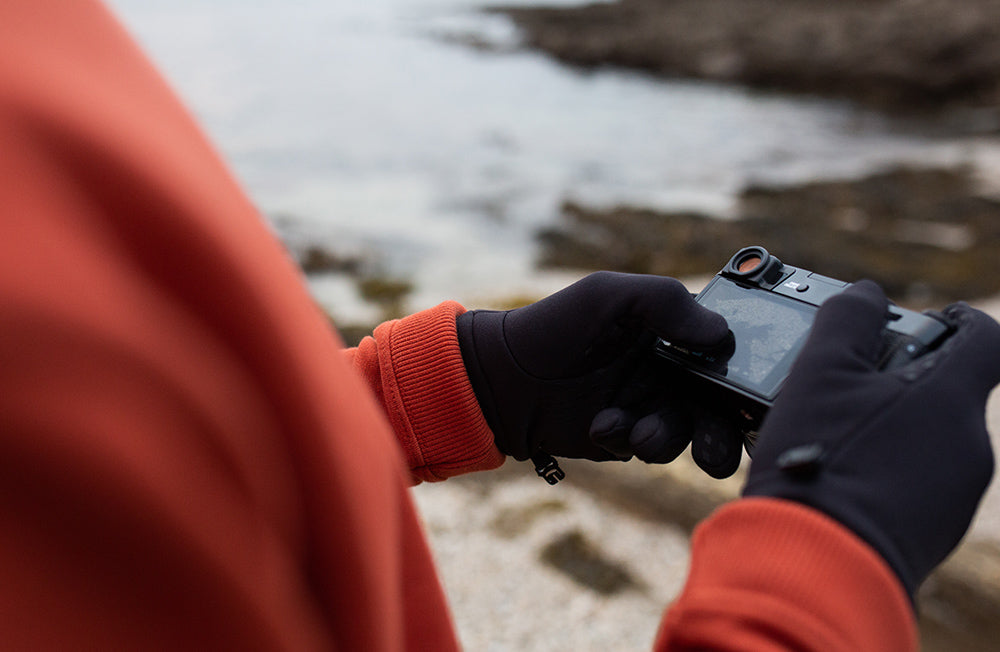 Man uses Passenger E-Tip gloves to touch the screen on his camera.
