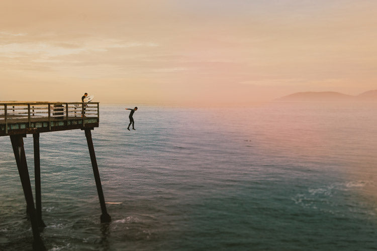 surfer jumping from a pier into the sea