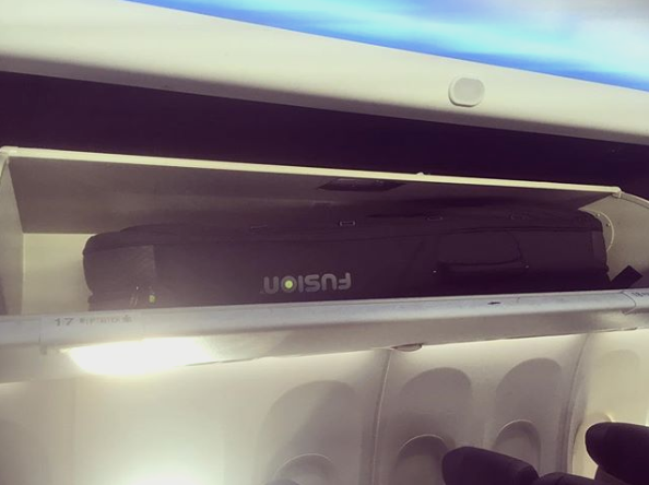 A Fusion Double Guitar Bag in an overhead bin at Southwest Airlines
