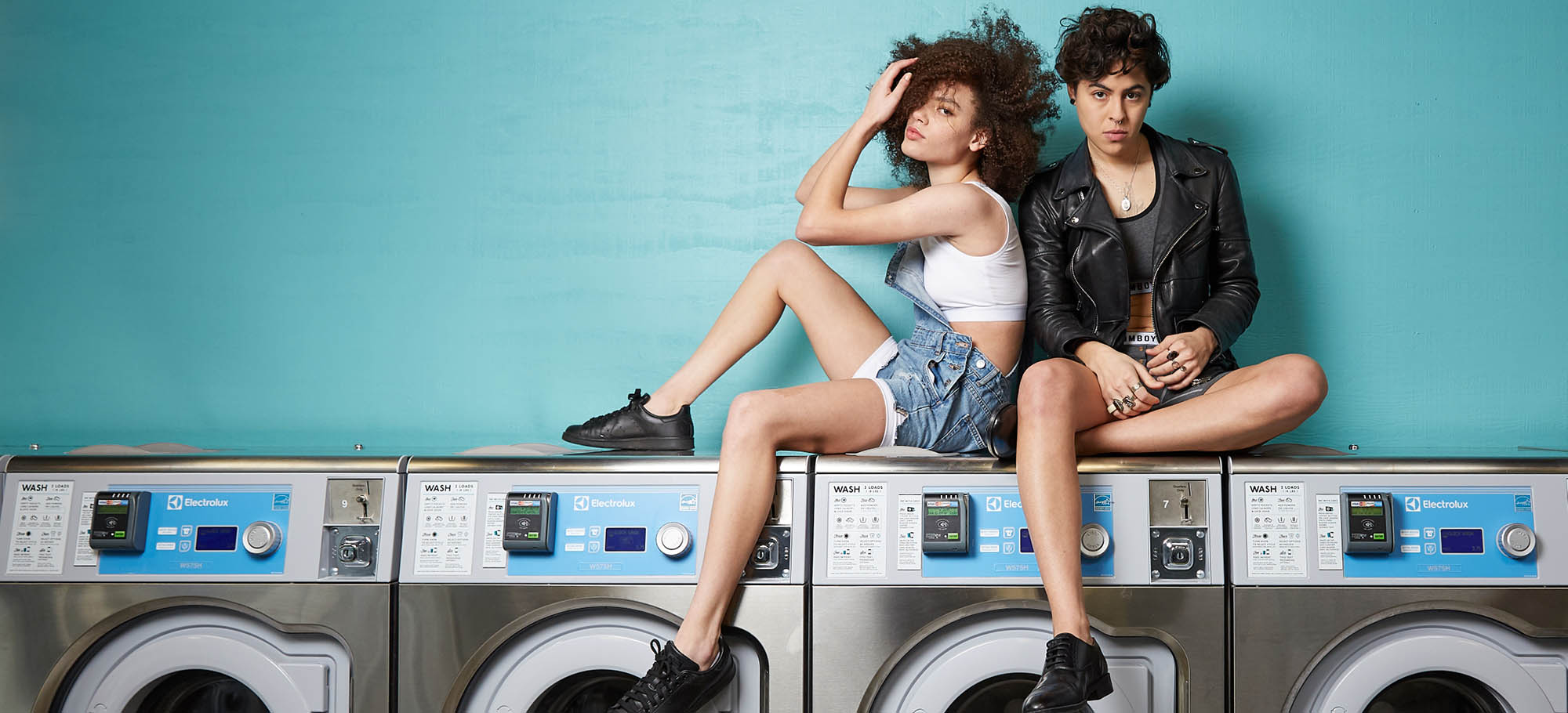two people sitting on washing machines