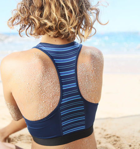 a woman sits on the beach in a TomboyX swimsuit