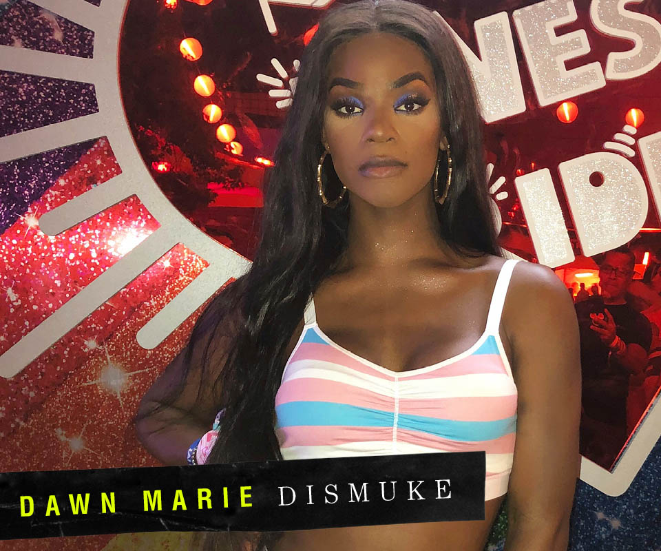 Dawn standing in front of a red background wearing the Trans Flag bra from TomboyX