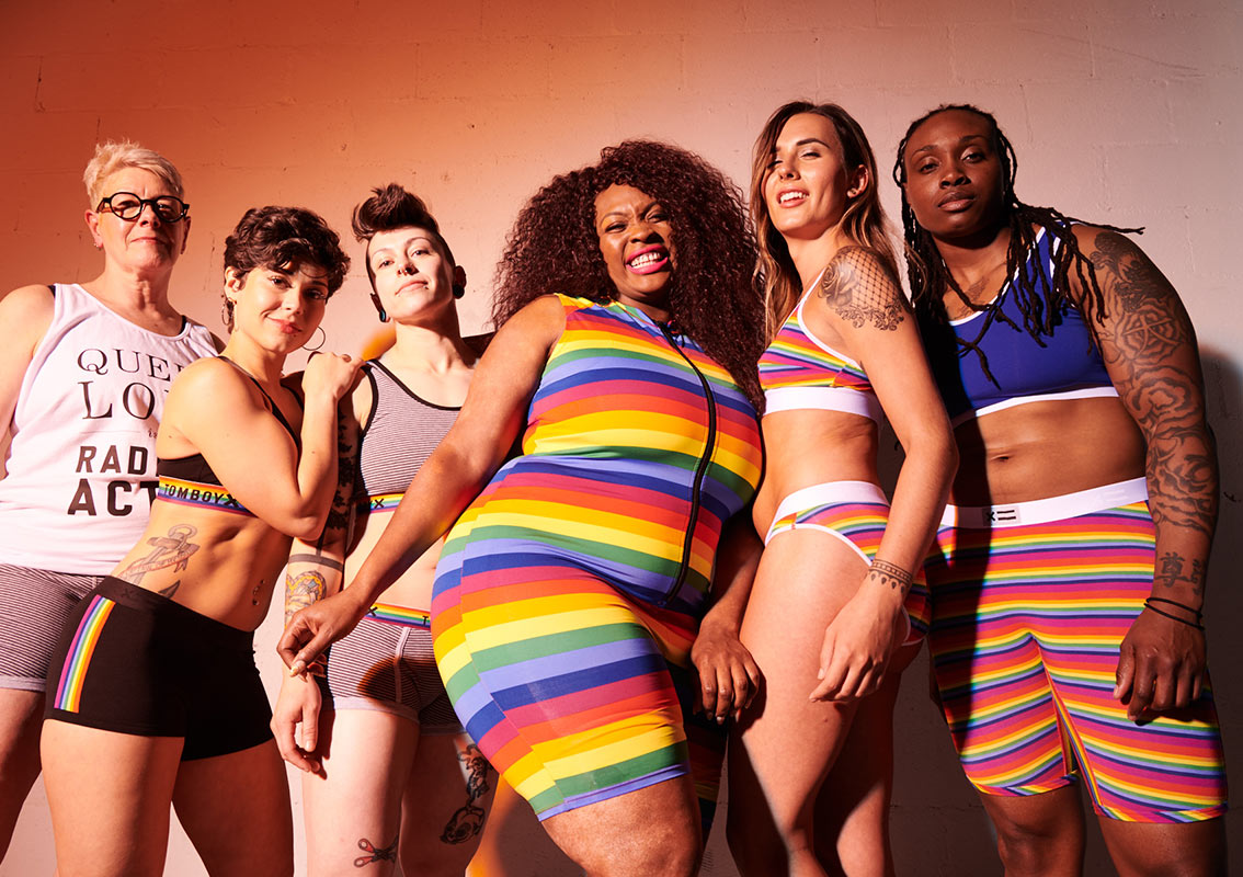 Group wearing TomboyX rainbow underwear and apparel.