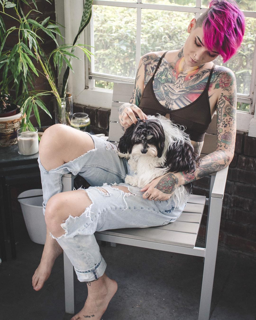 Wearing bralette sitting in a chair with a dog