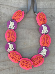 Tania Tupu's handwoven very bright Tiki Necklace  Hands down the brightest necklace in the collection.  Designed to stand out and catch the eye. Be brave!  Wearable handcrafted 3-dimensional 30mm Tiki beads woven together with double-sided silk ribbon and finished with an adjustable toggle.