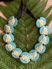 Wearable handcrafted 3-dimensional 30mm Tiki beads woven together with double-sided silk ribbon and finished with an adjustable toggle.