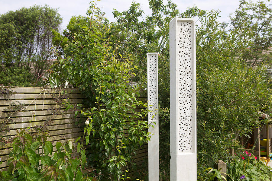 Beepost bee tower in green landscaping