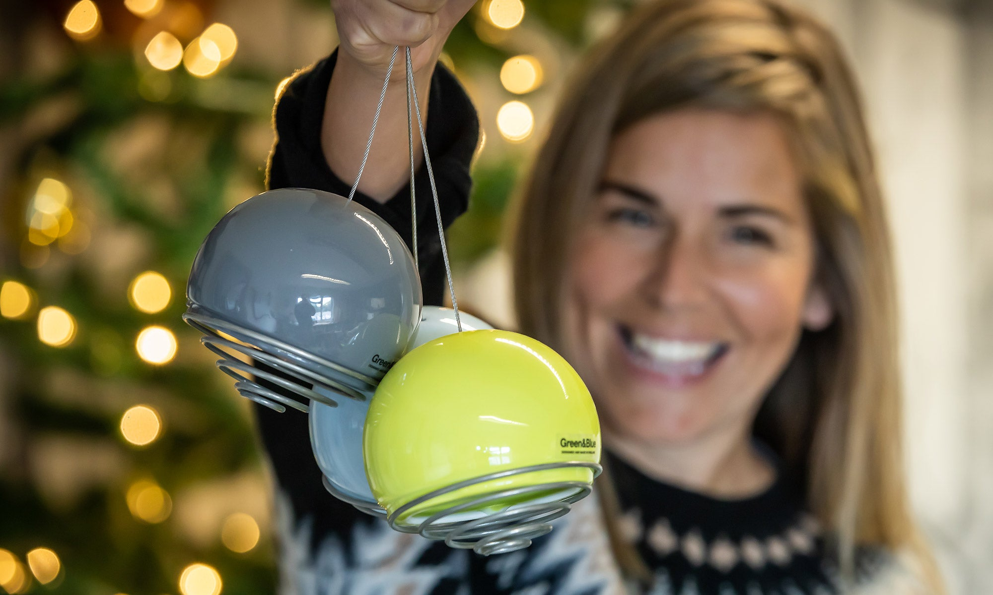 Smiling Lady holds 3 belle birdfeeders with christmas lights in the background