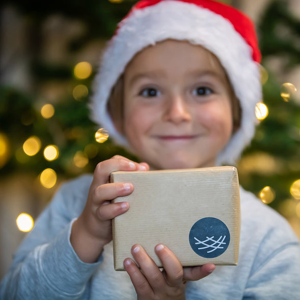 Boy holding a Green&Blue gift wrapped present and wearing a Christmas hat