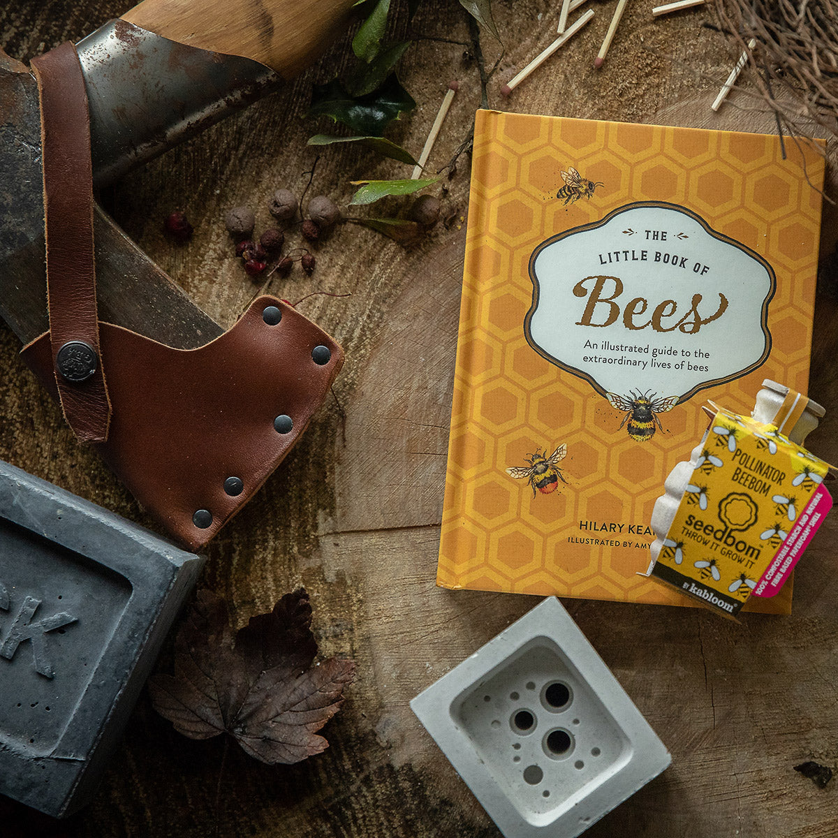 Bee lover gift bundle including bee hotel, book and wildflower seeds, shown on wooden background