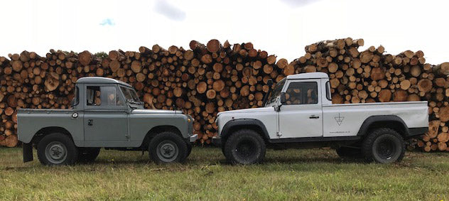 Landrovers in front of log pile