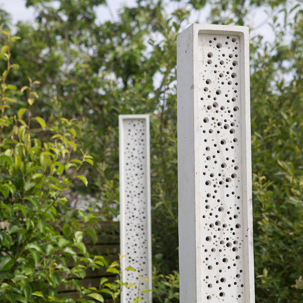 stylish bee post bee towers in wildflower garden