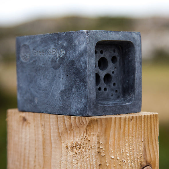 charcoal bee block in garden on fence