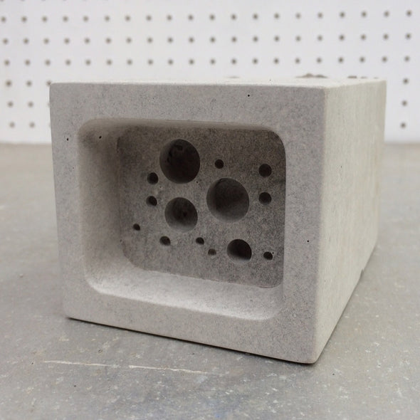 small bee block against pegboard background