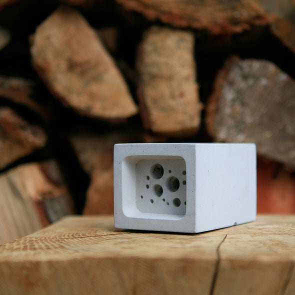 small bee block against wood pile