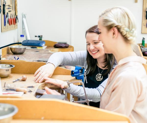 London Jewellery School founder Jessica Rose with a student at a jewellery workbench in the London Jewellery School 10th birthday celebration post