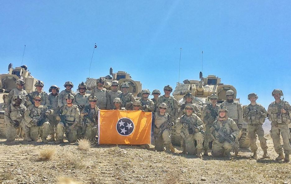 United States of American Soliders in a group holding a Volunteer Traditions Orange Tennessee State Flag.