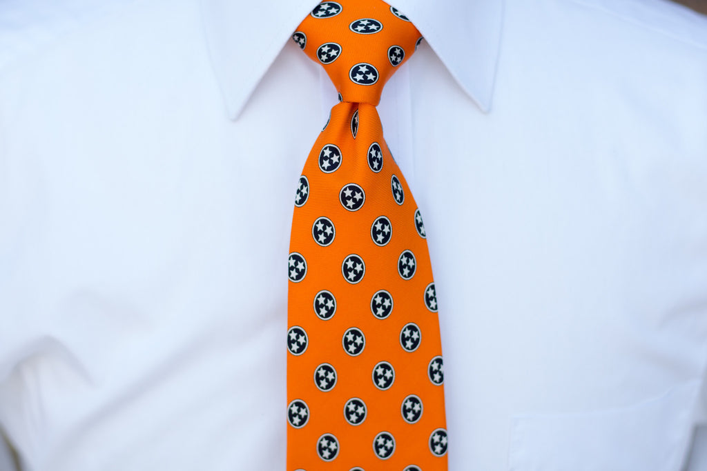 Volunteer Traditions Orange Tristar Tie on neck.