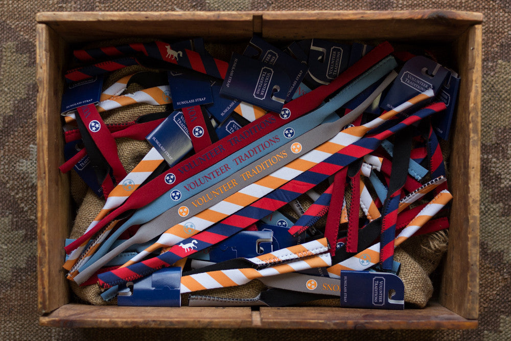 Volunteer Traditions Tristar Croakie Sunglasses Straps. Grey with Orange, Red with Navy, Navy with Gold, Stone Blue with Navy, and Orange and White Stipped Tristar Sunglass Straps in a box.