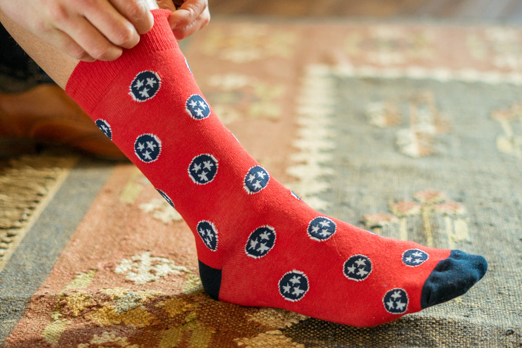 Volunteer Traditions Red with Navy Tristar sock on foot.