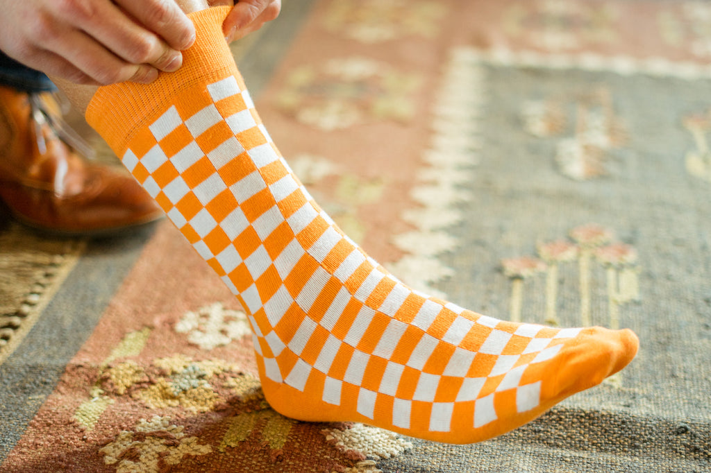 Volunteer Traditions University of Tennessee Licensed Socks. Orange and White Checkerboard sock bundle on foot.