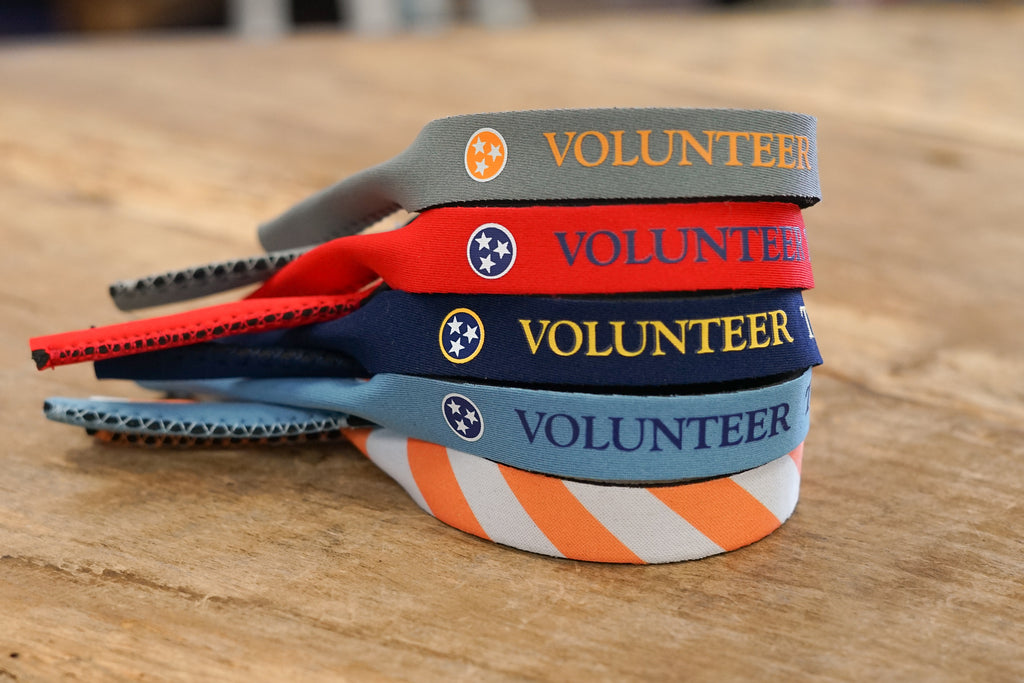 Volunteer Traditions Tristar Croakie Sunglasses Straps. Grey with Orange, Red with Navy, Navy with Gold, Stone Blue with Navy, and Orange and White Stipped Tristar Sunglass Straps stacked on wood.