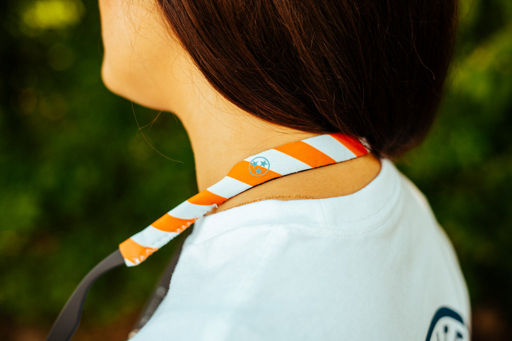 Volunteer Traditions Orange and White Striped Croakie Sunglass Straps around neck holding glasses.