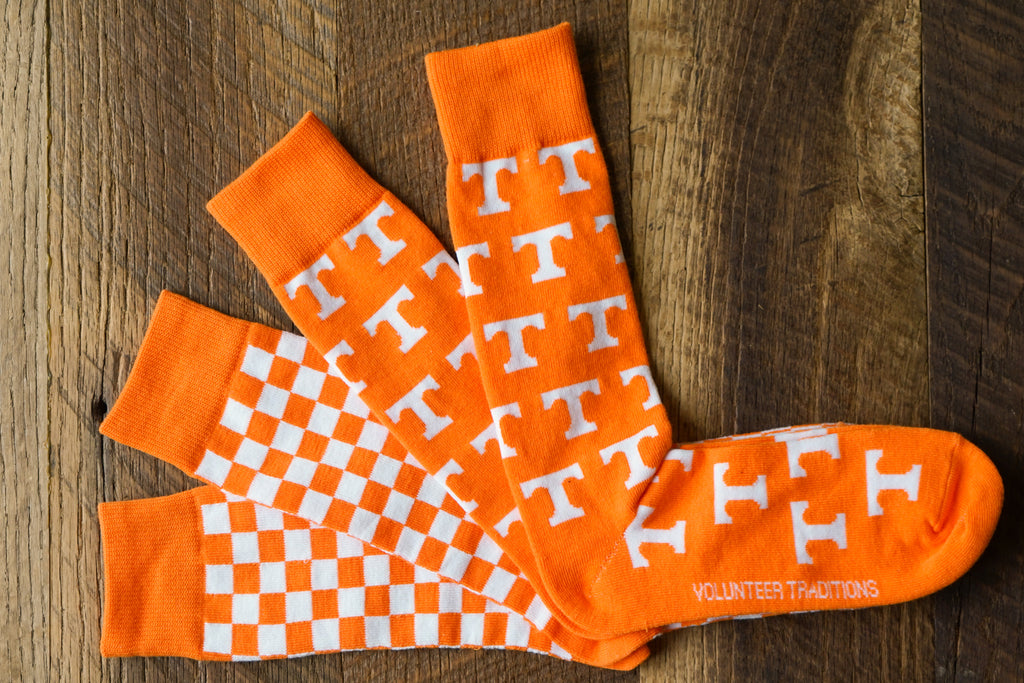 Volunteer Traditions University of Tennessee Licensed Socks. Orange Power T and Orange and White Checkerboard sock bundle on wood.
