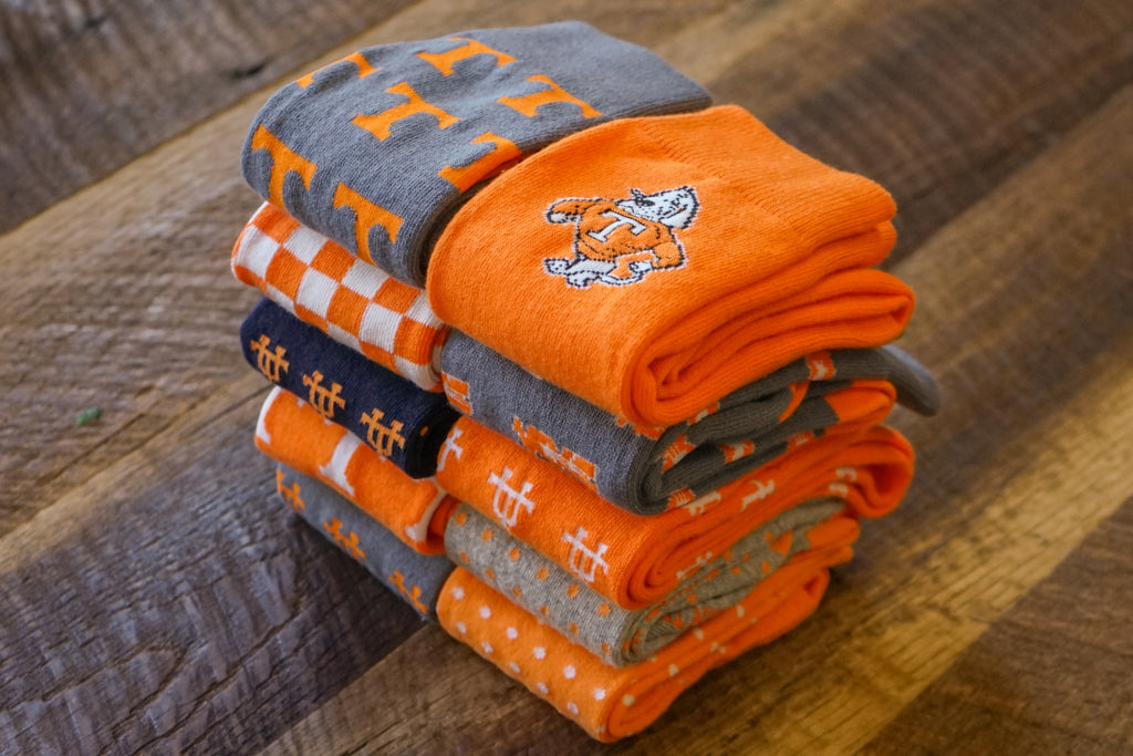 Volunteer Traditions University of Tennessee Licensed Socks. Grey Power T, Orange Smokey, Grey Star Vols, Orange Interlocking UT, Orange and White Checkerboard, Navy Interlocking UT, Orange Power T, and Grey Interlocking UT Socks on wood.