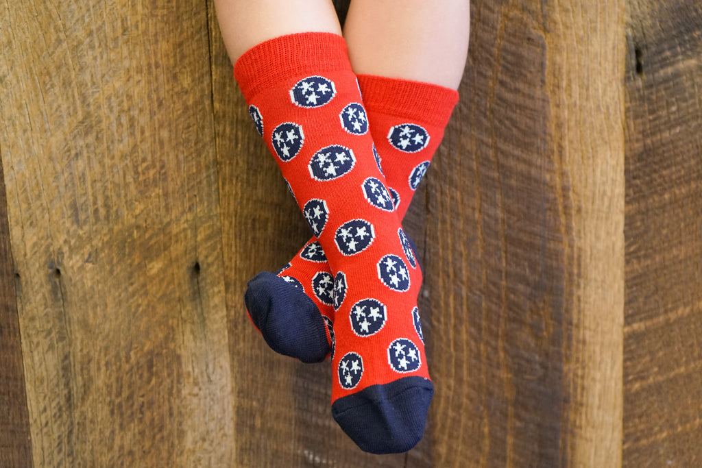 Volunteer Traditions Red and Navy Kid's Tristar Socks on Kids Feet.