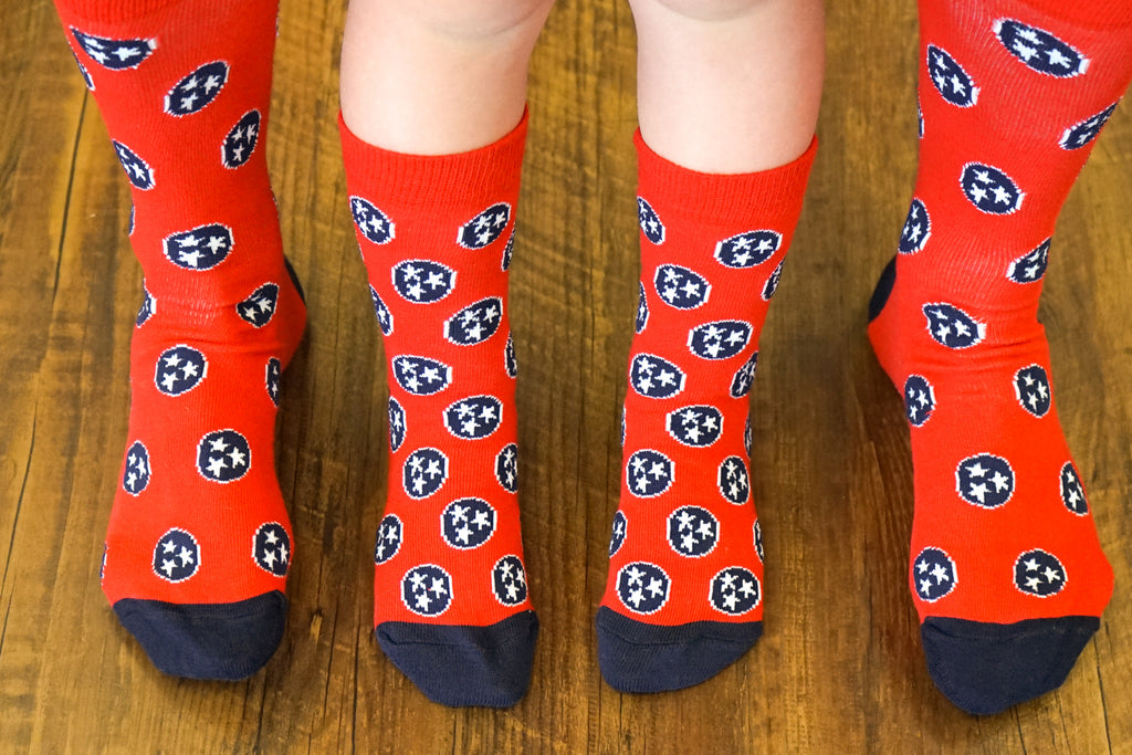 Volunteer Traditions Red and Navy Kid's Tristar Socks on Kids Feet next to Adult Feet for comparison.