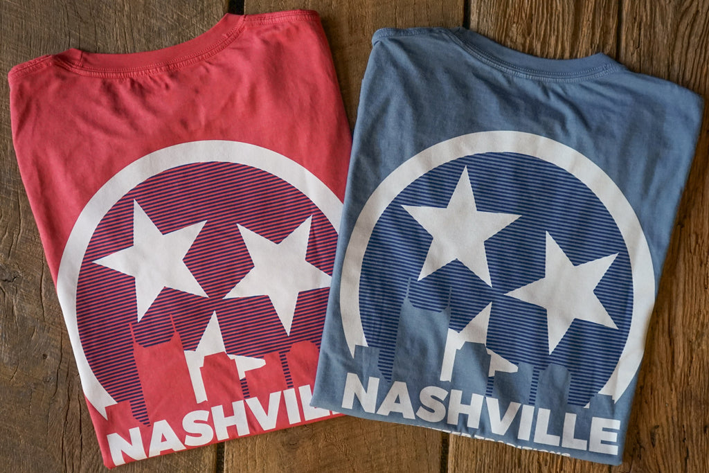 Volunteer Traditions Nashville Short Sleeve Pocket Tees in Red and Stone Blue on wood flat lay.