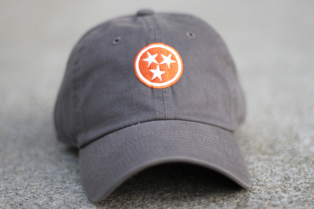Grey with Orange Tristar Tennessee Hat Flag Volunteer Traditions on concrete.